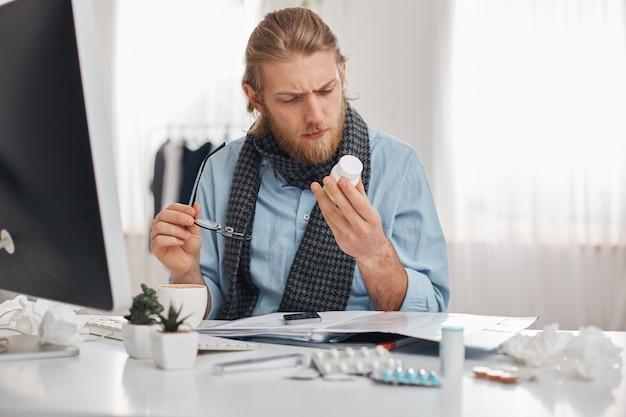 Kranker bärtiger männlicher büroangestellter in blauem hemd und schal mit brille konzentrierte sich auf das lesen der verschreibung von pillen. junger manager mit grippe, sitzt am arbeitsplatz, umgeben von drogen, tabletten, vitaminen