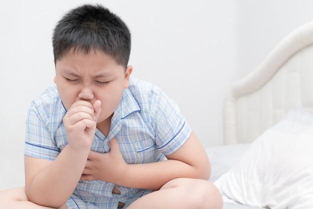 Kranker beleibter junge ist husten- und kehlinfektion auf bett, gesundheitswesenkonzept