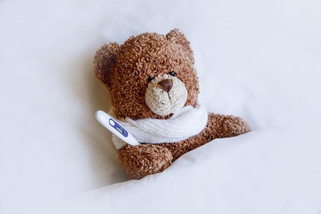 Kranker brauner teddybär mit thermometer