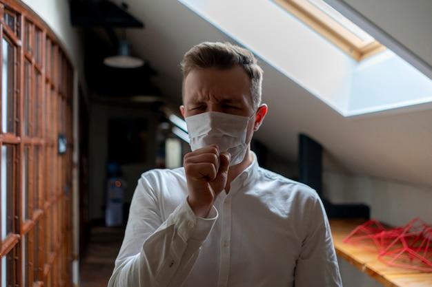 Kranker geschäftsmann in seiner schutzmaske der büroabnutzung. krankheitskonzept