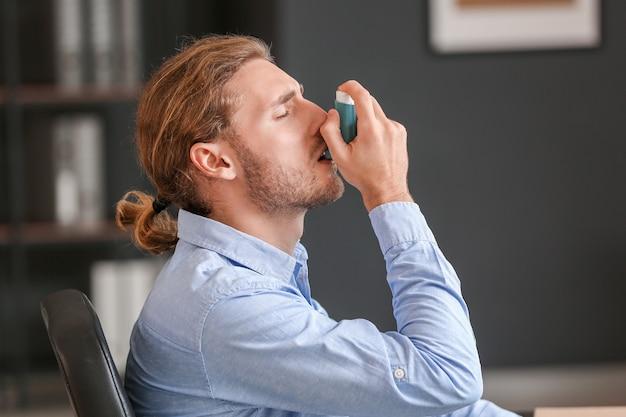 Kranker geschäftsmann mit inhalator im amt