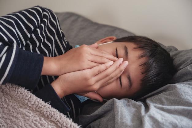 Kranker jugendlicher asiatischer junge, der eine maske trägt und im bett husten