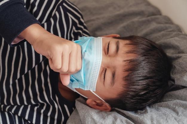 Kranker jugendlicher junge, der eine maske trägt und im bett husten