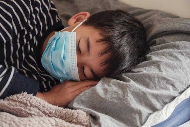 Kranker jugendlicher junge, der eine maske trägt und im bett stillsteht