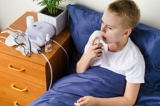 Kranker junge atmet durch vernebler, inhalator zur vorbeugung der behandlung.