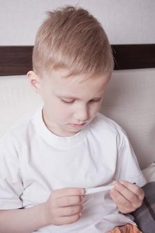 Kranker junge, der im bett sitzt und digitalen thermometer betrachtet