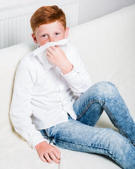 Kranker junge des mittleren schusses auf dem sofa