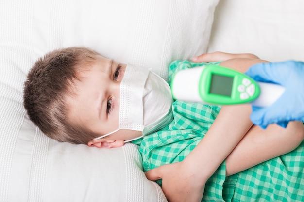 Kranker junge misst die temperatur mit einem thermometer