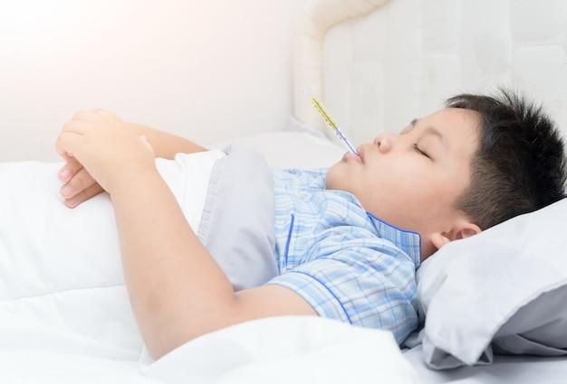 Kranker junge mit thermometerschlaf auf bett, gesundheitswesenkonzept