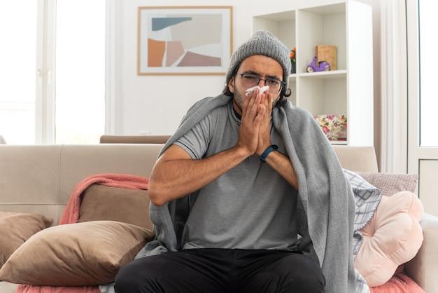 Kranker junger kaukasischer mann in optischer brille, eingehüllt in karierte wintermütze, wischt sich die nase mit taschentuch ab und schaut auf die kamera, die auf der couch im wohnzimmer sitzt