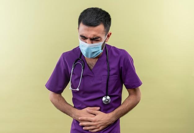 Kranker junger männlicher arzt, der lila chirurgenkleidung und medizinische stethoskopmaske trägt, packte schmerzenden magen auf lokalisiertem grünem hintergrund
