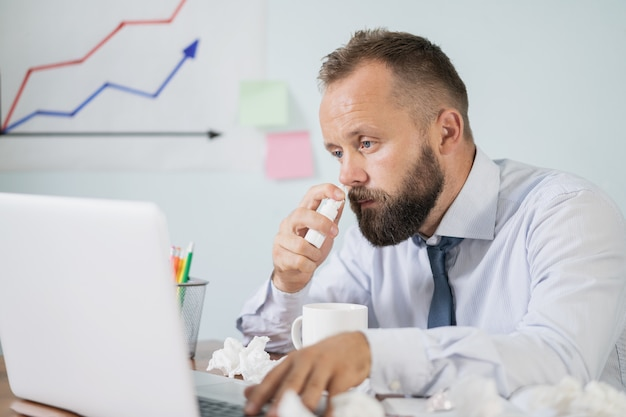 Kranker junger mann bei der arbeit bekam eine grippeallergie, niest, wischt sich die laufende nase im gewebe