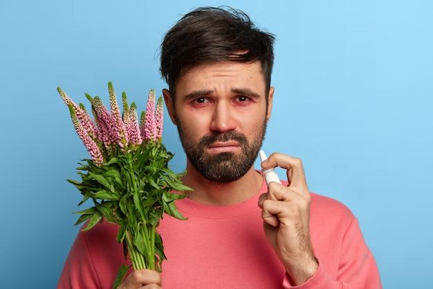 Kranker junger mann, der an allergie leidet, isoliert