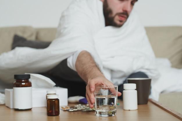 Kranker junger mann, eingewickelt in eine decke, die auf der couch sitzt und ein glas wasser vom tisch nimmt, während er schmerzmittel oder andere medizin nimmt