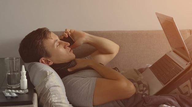 Kranker junger mann im bett, der am notebook arbeitet und telefoniert. viele pillen und medikamente liegen auf dem nachttisch. sonnenlicht