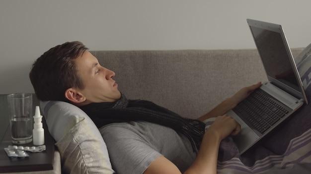 Kranker junger mann im bett, der an notebook arbeitet. viele pillen und medikamente liegen auf dem nachttisch.