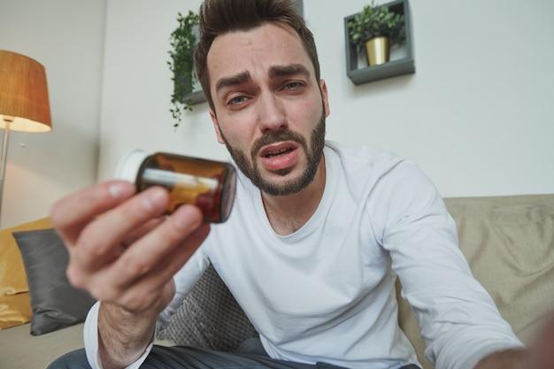Kranker junger mann mit erkältung, grippe oder coronavirus zeigt flasche mit pillen, die er nimmt, während er mit online-arzt vor laptop konsultiert