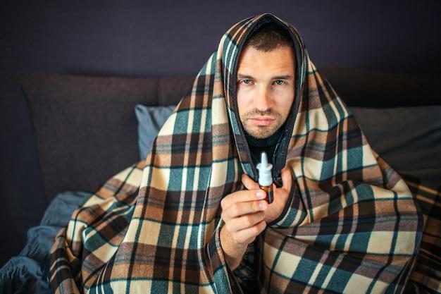 Kranker junger mann schaut vor der kamera. er hält nasenspray in der hand. guy meint es ernst, er ist komplett mit decke bedeckt. junger mann ist im schlafzimmer.