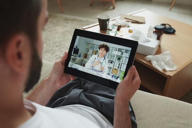 Kranker junger mann sitzt auf der couch und hält touchpad vor sich während der online-konsultation mit dem arzt, während er zu hause bleibt