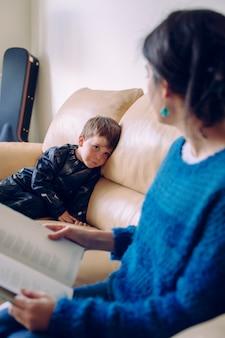Kranker kleiner junge, der eine geschichte aus einem buch hört. lebensstil mit kindern im haus. kleines kind zu hause geerdet. junge mutter liest ihrem kind die hausaufgaben ohne schulzeit vor.