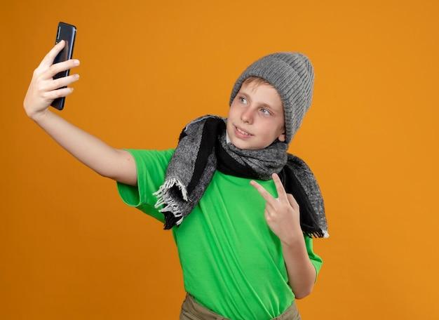 Kranker kleiner junge, der grünes t-shirt im warmen schal und im hut trägt, der sich besser hält, smartphone zu halten, das selfie tut, das v-zeichen zeigt, das über orange wand steht