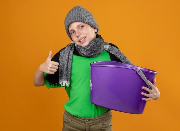 Kranker kleiner junge, der grünes t-shirt im warmen schal und in der mütze trägt und müll hält, der übel lächelnd zeigt, zeigt daumen hoch stehend über orange wand