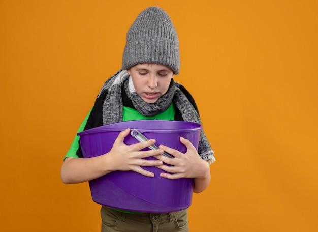 Kranker kleiner junge, der grünes t-shirt im warmen schal und in der mütze trägt und müll hält, der übelkeit fühlt, die über orange wand steht