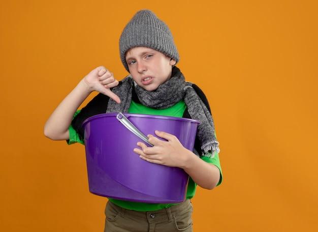 Kranker kleiner junge, der grünes t-shirt im warmen schal und in der mütze trägt und müll hält, der übelkeit zeigt, daumen unten unglücklich und krank stehend über orange wand zeigt