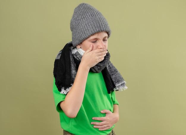 Kranker kleiner junge, der grünes t-shirt in warmem schal und hut hustet und sich unwohl fühlt, über heller wand stehend