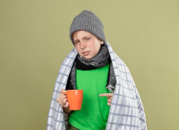 Kranker kleiner junge, der grünes t-shirt in warmem schal und hut in decke gewickelt hält tasse des heißen tees pointign mit finger an ihm unglücklich und krank steht über heller wand
