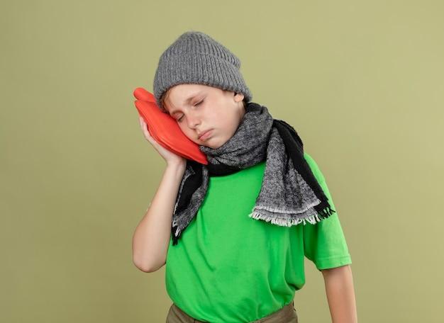 Kranker kleiner junge, der grünes t-shirt in warmem schal und hut trägt, die sich unwohl fühlen, wasserflasche haltend, um warmen lehnenden kopf darauf zu halten, der über heller wand steht