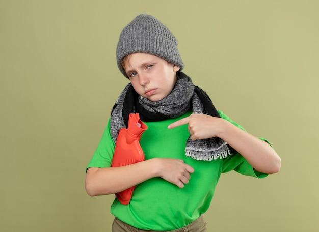 Kranker kleiner junge, der grünes t-shirt in warmem schal und hut trägt, die sich unwohl fühlen, wasserflasche zu halten, um warm zu halten, mit dem finger darauf zeigend über heller wand stehend