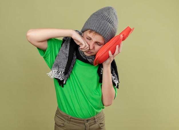 Kranker kleiner junge, der grünes t-shirt in warmem schal und hut trägt und sich unwohl fühlt, wasserflasche zu halten, um warmes leiden unter laufender nase zu halten, die über heller wand steht