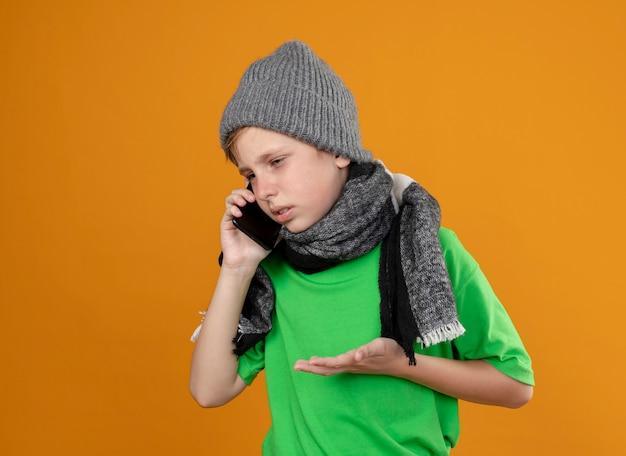Kranker kleiner junge, der grünes t-shirt in warmem schal und hut trägt und sich unwohl fühlt, wenn er auf handy spricht, das unzufrieden ist, über orange wand zu stehen