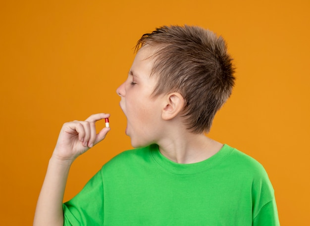 Kranker kleiner junge im grünen t-shirt, der sich unwohl fühlt, eine pille nehmend, die über orange wand steht