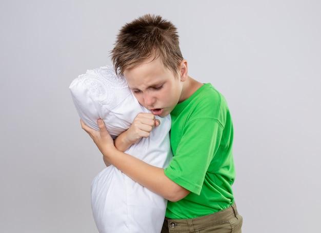 Kranker kleiner junge im grünen t-shirt, der sich unwohl fühlt, kissen hustend hustend stehend über weißer wand