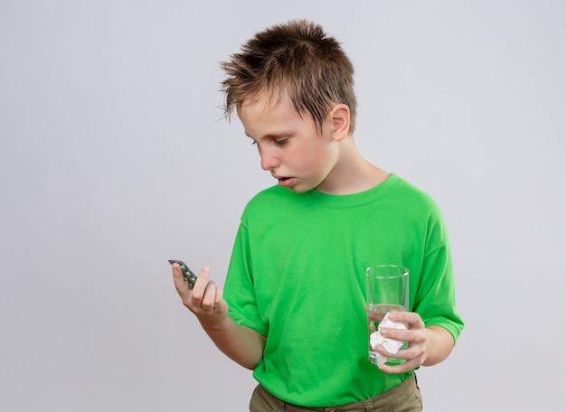 Kranker kleiner junge im grünen t-shirt, der sich unwohl fühlt, wenn er glas wasser hält, das pillen betrachtet, die über weißer wand stehen