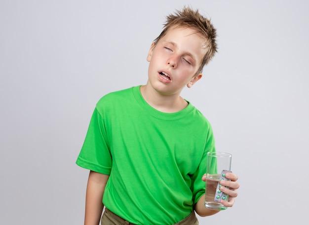 Kranker kleiner junge im grünen t-shirt, der sich unwohl fühlt, wenn er glas wasser und pillen hält, die unter kälte leiden, die über weißer wand stehen