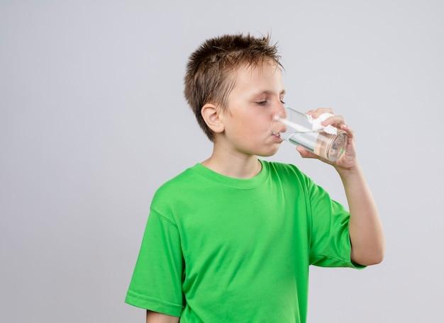 Kranker kleiner junge im grünen t-shirt, der untrinkendes wasser fühlt, das über weißer wand steht