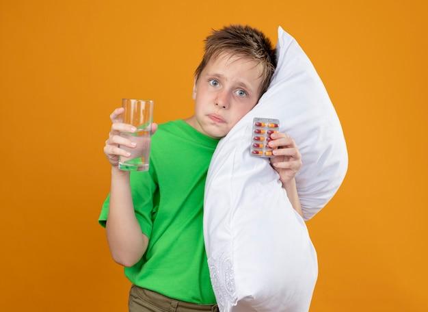 Kranker kleiner junge im grünen t-shirt fühlt sich unwohl, hält kissen und glas wasser mit pillen, die kopf auf kissen lehnen, verwirrt über orange wand stehend