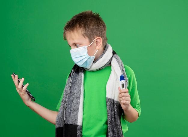 Kranker kleiner junge im grünen t-shirt und im warmen schal um seine halstragende gesichtsschutzmaske, die thremometer hält und sein smartphone betrachtet, besorgt über grünem hintergrund stehend