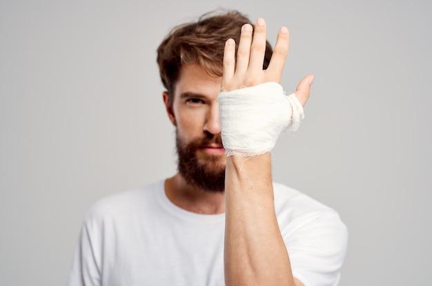 Kranker mann bandagierte handverletzung an den fingern krankenhausaufenthalt isolierter hintergrund