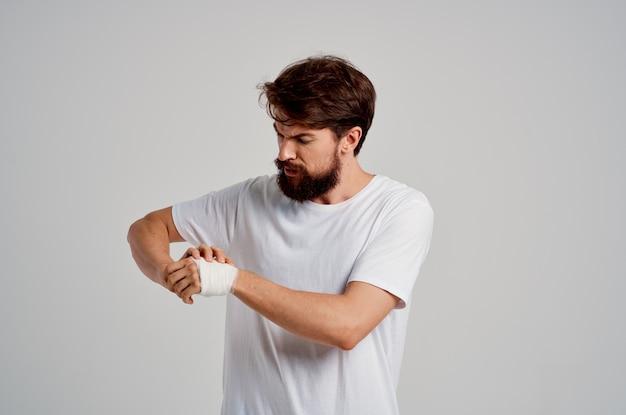 Kranker mann bandagierte handverletzung an fingern krankenhausaufenthalt heller hintergrund