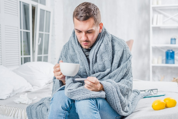 Kranker mann, der auf dem bett hält tasse kaffee überprüft das fieber im thermometer sitzt
