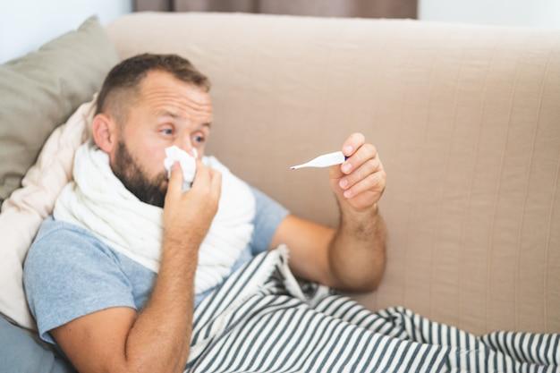 Kranker mann, der auf dem sofa zu hause überprüft seine temperatur im wohnzimmer liegt