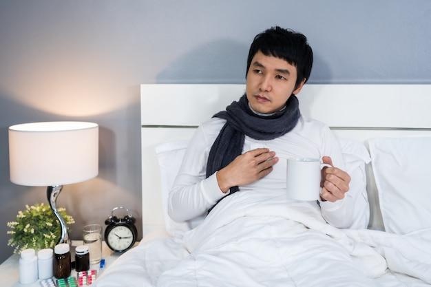 Kranker mann, der eine tasse heißes wasser auf bett trinkt