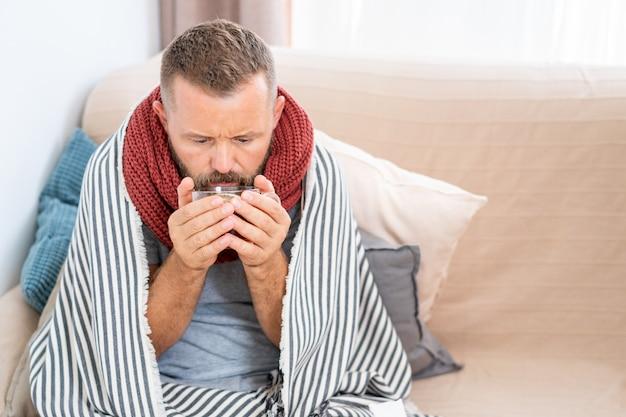 Kranker mann, der fieber hat und heißen heilenden tee trinkt