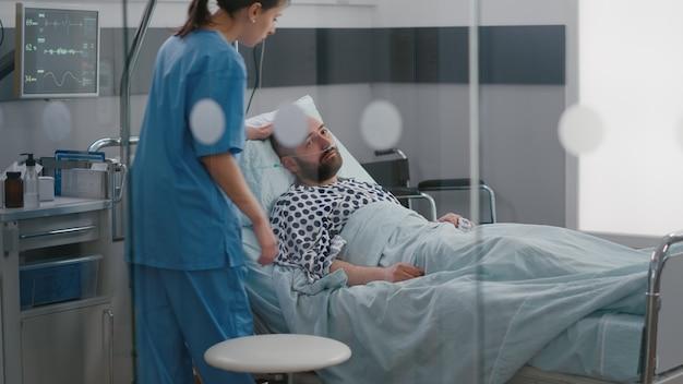 Kranker mann, der im bett ruht und eine nasensonde trägt, wartet auf einen arzt für die krankheitsuntersuchung