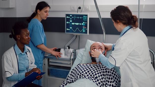 Kranker mann, der im bett ruht, während die medizinerin die sauerstoffmaske aufsetzt und die atemwegssymptome überprüft. arzt, der während des genesungstermins eine krankheitsbehandlung schreibt, die in der krankenstation arbeitet