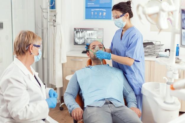 Kranker mann, der sich auf eine zahnoperation vorbereitet, während die krankenschwester während des stomatologischen krankenhausbüros eine medizinische sauerstoffmaske auf dem zahnarztstuhl aufsetzt